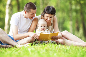 Happy family reading book in park