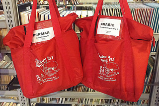 "Two red bags containing books, one labeled ""Persian"" and one labeled ""Arabic"""