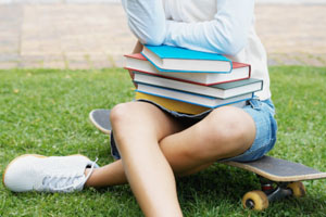Young woman sitting on skateboard with books