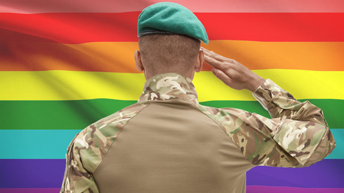 service member saluting in front of gay pride flag