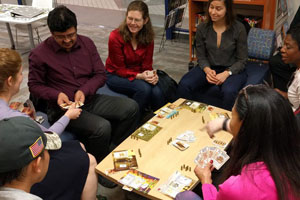 Adults sitting around a low table playing a game with cards and game pieces