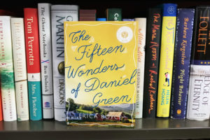 "photo of ""Fifteen Wonders of Daniel Green"" leaning against other books on a shelf"