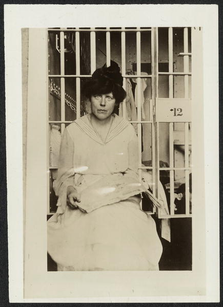Informal portrait, Lucy Burns, three-quarter length, seated, facing forward, holding a newspaper in her lap in front of a prison cell, likely at Occoquan Workhouse in Virginia.