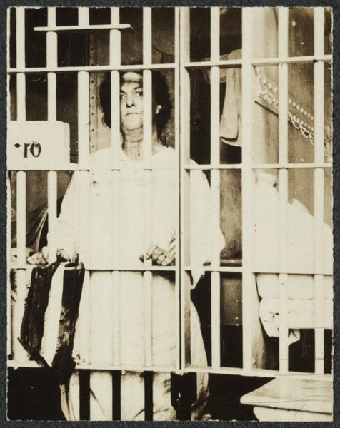 Photograph of Helena Hill Weed, facing forward, standing behind bars in a prison cell.