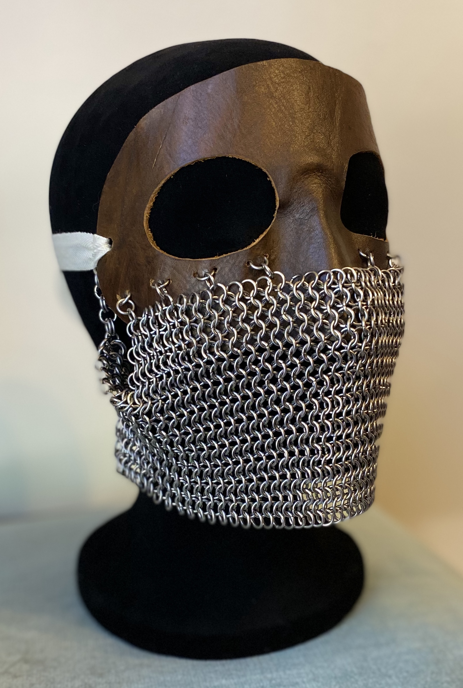 "Stainless steel European 4-in-1 chain weave; wet-molded leather; cotton. I have been making chainmaille and scale maille pieces for roughly eight years. This is not the greatest skill to have when making masks to combat viral infections. Nevertheless, I Googled ""chainmaille mask"" to see what was out there, and I was immediately struck by World War One-era tank masks. These masks were worn by tank gunners to protect their faces against schrapnel. They are heavy and strong and yet vulnerable to other dangers of war, such as poisonous gas and infection. I knew I immediately had to make one of these masks to manifest some of my pandemic emotions."