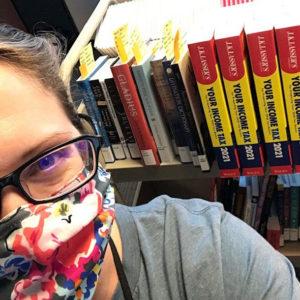 Cataloger taking selfie with book truck full of books.