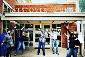 Library staff stand outside of Westover pointing at the front door, looking excited.