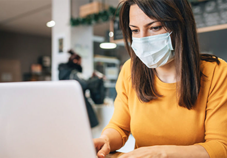 Woman typing on a laptop in a coffee shop while wearing a face mask
