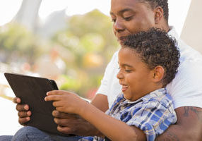 father and son reading on a portable computer