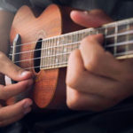 close up view of a ukulele being strummed